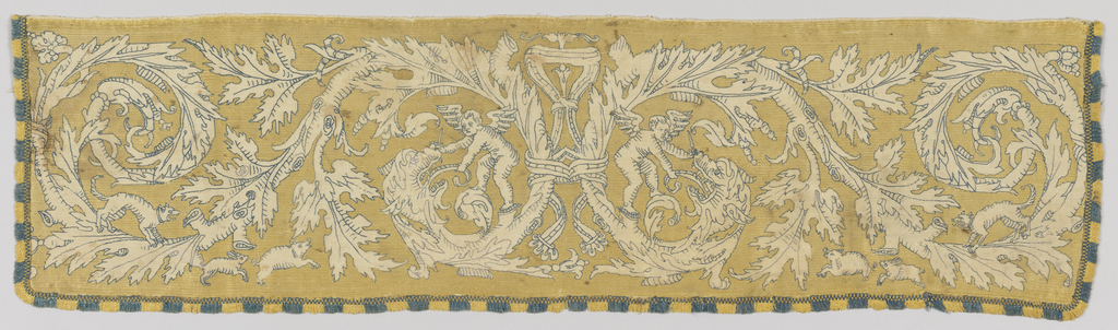 Symmetrical design of curving branched with acanthus leaves, each branch forming a large horizontal S-shape. One end of each branch turns into a grimacing beast whose tongue is being grasped by a standing winged cupid. The positive space in the design is the natural linen foundation; the negative space is solidly worked yellow silk long-legged cross-stitch. The design is outlined and accented by blue silk outline stitch, and there is a short thick blue and yellow silk fringe on three sides.