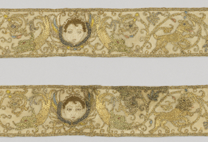 A pair of narrow borders of cream-colored linen elaborately embroidered in gold thread and colored silk. Design shows a winged head of cherubim with a symmetrical border pattern of dolphins, lions, and a vase of flowers with delicate symmetrical vines framing and connecting the elements. Faces of cherubs in white silk, long and short stitch, with dark brown for curly hair. Balance of the design in couched gold thread, partly with color. Manes of lions in heavy, looped gold. Flower heads in colored silks in pale tints.