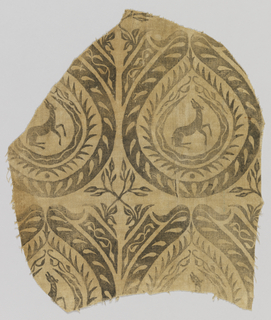 Fragment of printed linen with gazelles in tear-shaped medallions, with crossed plant forms in interstices, in gold on an off-white ground.