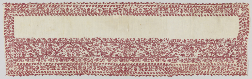 Panel made by piecing together two ends of an embroidered towel. The smaller pattern is of a curving vine and pomegranate; the larger pattern has a curving vine and fruiting plant. Embroidered in red on an off-white ground, with red and white lace edging at top and bottom.