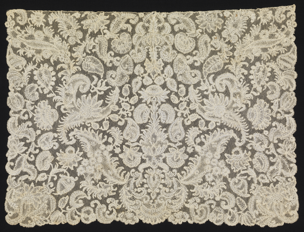 Brussels-style cravat  with a central, urn-shaped motif composed and surrounded by symmetrically arranged floral and foliated forms.