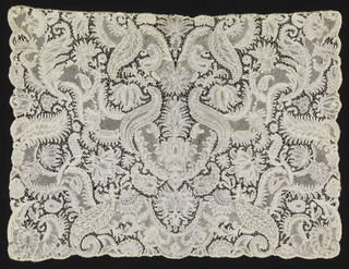 Cravat end of Brussels-style lace with a design of undulating, foliated pattern entwined and surrounded by symmetrically arranged floral and foliated forms.