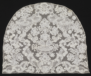 Cap crown  with a central design of flowers in a vase, symmetrically framed by floral sprays and cartouches.