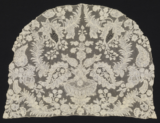 Cap crown of Brussels-style lace. Symmetrical arrangement of bowl of flowers surrounded by leaf forms