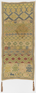 Long vertical sampler with horizontal bands of geometric pattern in blue, green, yellow, red and pink on a natural ground. Trimmed with two tassels at bottom.