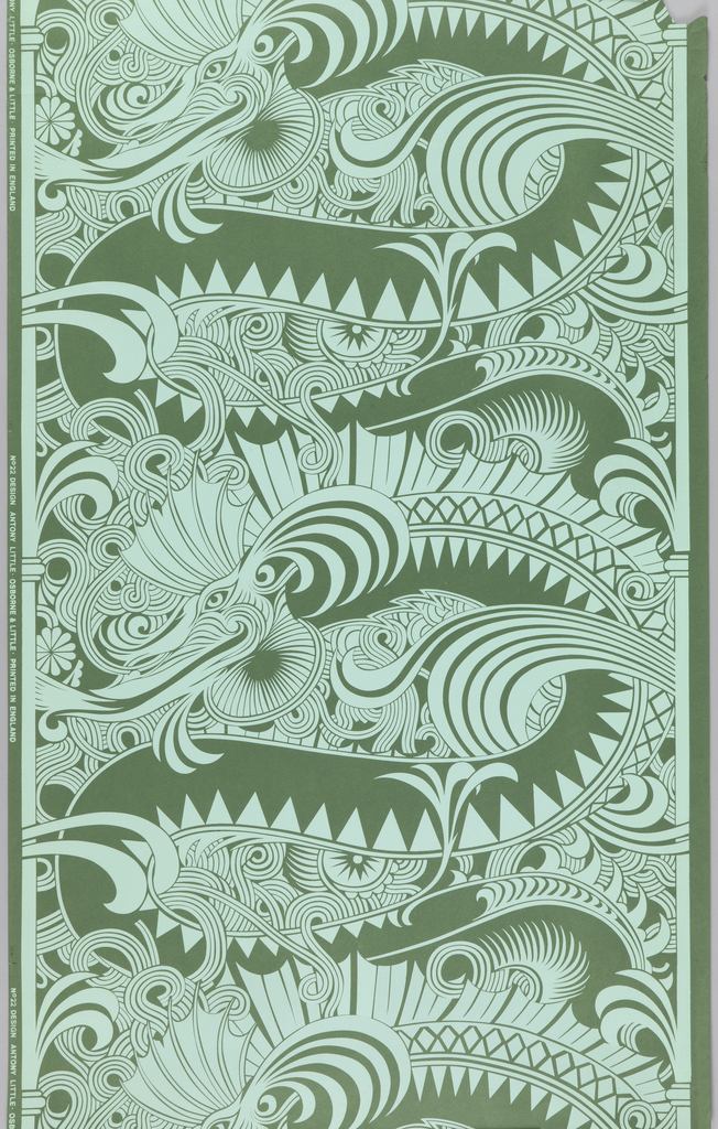 On green construction paper, pale bluish-green swirling pattern of large scale dragons, vertically repeated, between column-like vertical edgings.