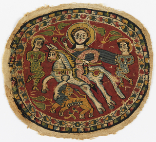 Tapestry medallion with polychrome figures on a red ground. In the center field, a haloed rider on a prancing horse carries a staff or scepter topped with a trefoil, and holds a ring. A lion below looks back over his shoulder. Two additional figures, one at each side, wear spotted green clothing. The rider is in pink with a flowing blue cape. Inner border of polychrome connected flower heads on a natural ground; outer border of polychrome stepped pattern on dark blue ground.  The image is said to represent the emperor with two Persian prisoners, a reference to the victory of Heraclius (617 - 641) over the Persians in 627.
