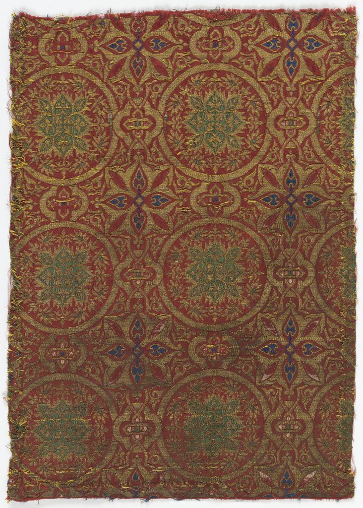 Fragment of woven silk with a pattern floral medallions in a framework of circles, eight-pointed stars and strap work in green, blue, gold and white on a red ground.