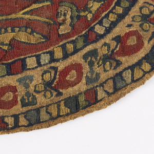 """Tapestry medallion of very fine weave with blue and tan figures on a red ground. Two confronted horsemen flank a tree; they wear a green and blue tunic, respectively, and carry swords and shields rimmed with pearl bands and their cloaks stream out behind them. Above the horsemen, a pair of horizontal branches terminating in heart-shaped leaves support a pair of confronted animals, heads reversed. A human head in the field under each horseman. The inner border contains vegetal motifs, including heart-shaped flowers and trefoils. Inner and outer degraded """"pearl"""" borders."""
