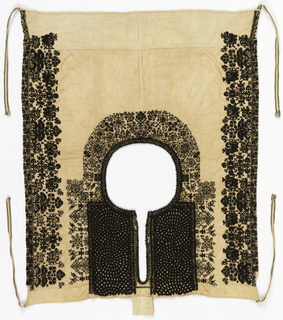 Vestee of heavy cream-colored linen embroidered in black wool. The round neck opening has a deep slit in the front which is embroidered on both sides with wide bands of heavily worked spirals. Around the collar are cross-stitched designs of stylized plants and birds. Both sides, corresponding to the shoulder area, have broad bands of stylized plant forms and small stags.The vestee is pulled over the head and tied at the sides with black and white tapes.