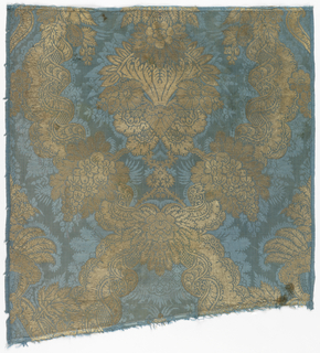 Large scale design, symmetrical around the center line of the fabric. A heavy floral form enclosed within an ogival framework of twisted ribbons and flowers. In gold on a medium blue damask ground.