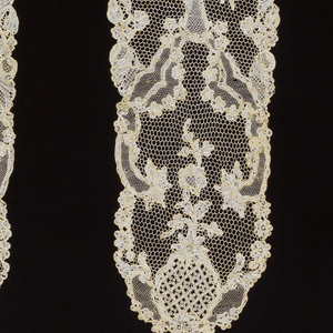 Pair of cap streamers of Point d'Argentan with an open floral pattern contained within compartments and alternated with medallions.