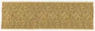 Band of light brown linen with a stylized vine pattern embroidered in brown and yellow.