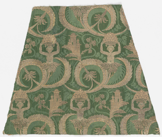 Fragment of green silk damask brocaded in gold and rose. Symmetrically entwined foliage, grotesque figures and a tower.