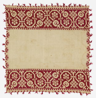 Cover showing a geometric vine pattern at each end. Small red tassels on all four sides.