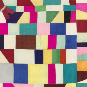 A multi-color patchwork of silk squares, rectangles and triangles in blues, greens, yellows, oranges, pinks and white. The design gives the appearance of radiating out from the center, with the smallest pieces in the center and growing slightly larger with each concentric square. Off-white lining.
