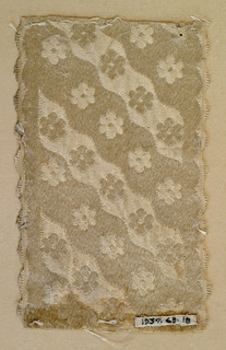 Ivory ribbon of the same design as 1937-63-17. Alternate wavy bands of satin and plain cloth weave. Scalloped edges.