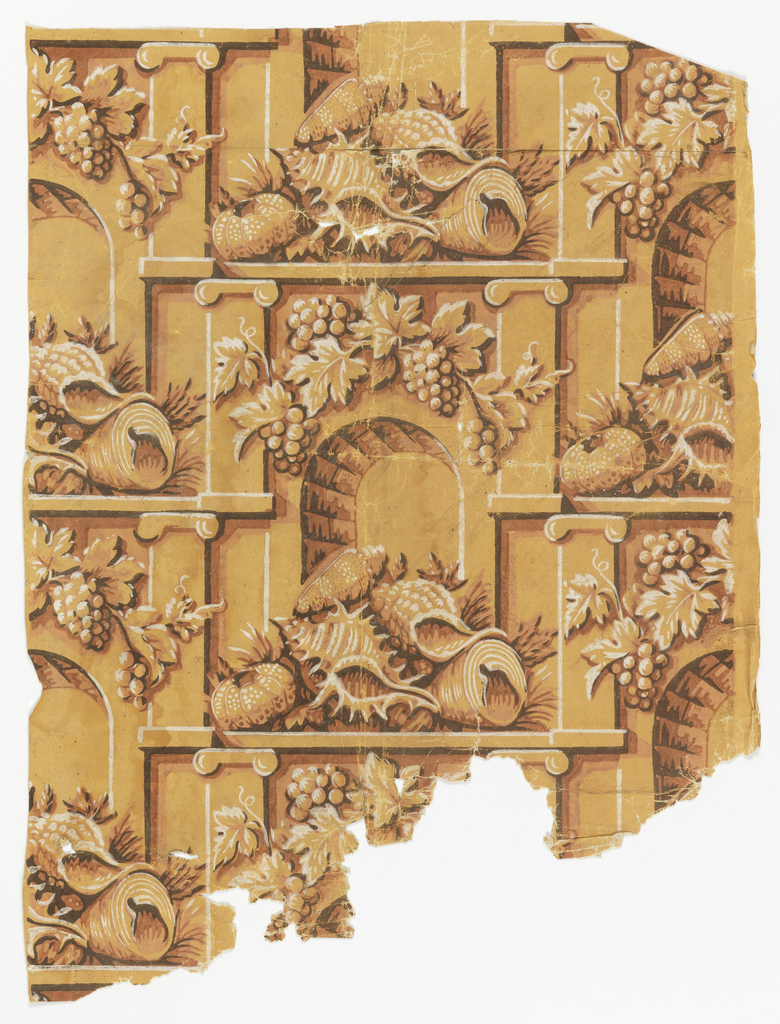 Pillar and arch design. A pile of shells sits on a ledge before an arch. The arch is fronted by a pilaster on either side. Bunches of grapes hang from a vine over the arch. The interior shows a brick pattern. Printed in off-white and shades of brown on a yellow ocher ground.