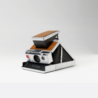 Camera open: Angular metal-covered plastic body, the triangular, hinged bellows and lens housing rising from flat rectangular base, and surmounted by angled view finder; tops of view finder and bellows housing covered in tan leather. Recessed circular lens, red shutter button, and other controls at front of housing. Base opens at front to accept film casette.  Camera closed: flat rectangular metal form surmounted by flat rhomboidal folded view finder cap; tops of view finder and housing covered in tan leather.
