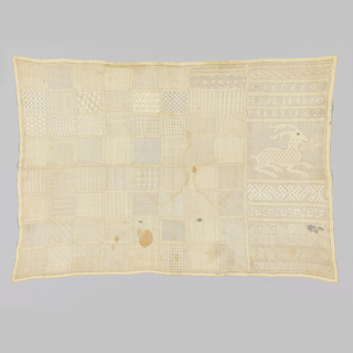 Seventy-one squares and bands of pattern as well as a deer and an alphabet in withdrawn element work in white.  The mouth and the eye of the deer are in colored silk.
