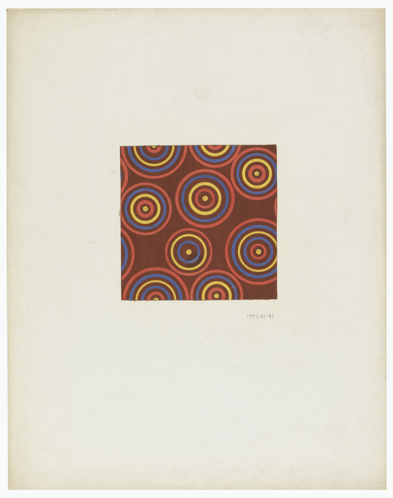 On brown background, concentric circles of various sizes painted in red, yellow and blue.
