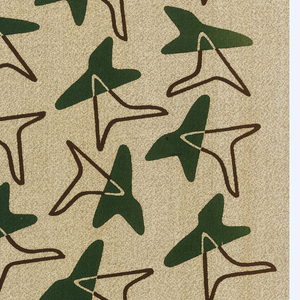 Repeating design of an outlined brown boomerang (or shark tooth) shape superimposed on a solid green boomerang (or shark tooth) shape, on a mottled tan ground.