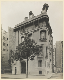 Photograph of the exterior facade of Hector Guimard's house, a four story dwelling situated at the corner of Rue Mozart in Paris. Constructed of brick with limestone trim and cast bronze balconies.