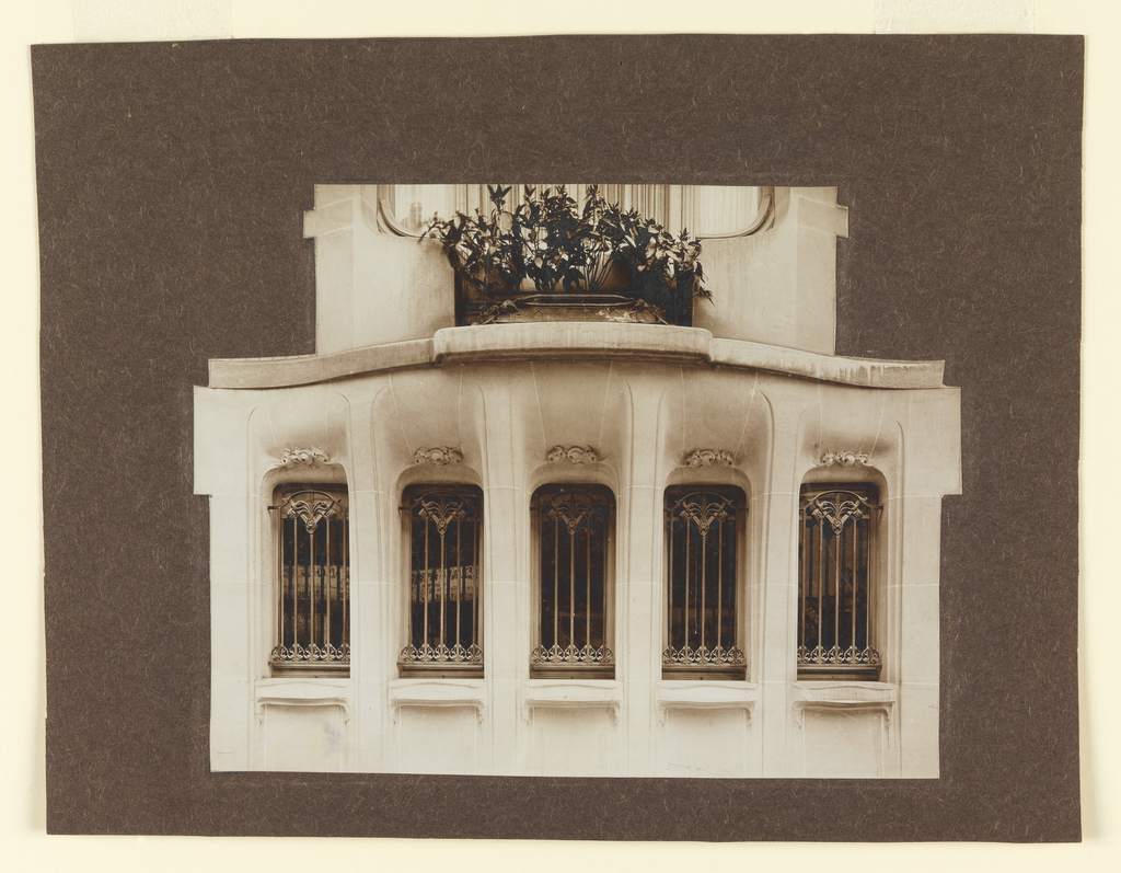 Five deeply set vertical windows protected by cast bronze grillework. Above, a balcony with a low orange tree on it. The limestone framework is carved with Guimard ornamentation. Side windows, not facing rue Mozart.