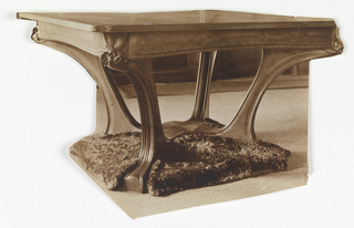 A photograph of a table designed by Hector Guimard. The elongated legs of the table curve inward and attach to a solid base.