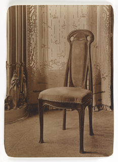 A photograph of a chair designed by Hector Guimard, which has an ornamented back and is upholstered with fabric.