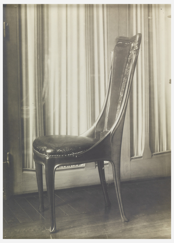 A photograph of a chair designed by Hector Guimard, shown in profile. The sides of the chair slope down to attach to the seat. A glass door with a curtain behind it appears in the background.