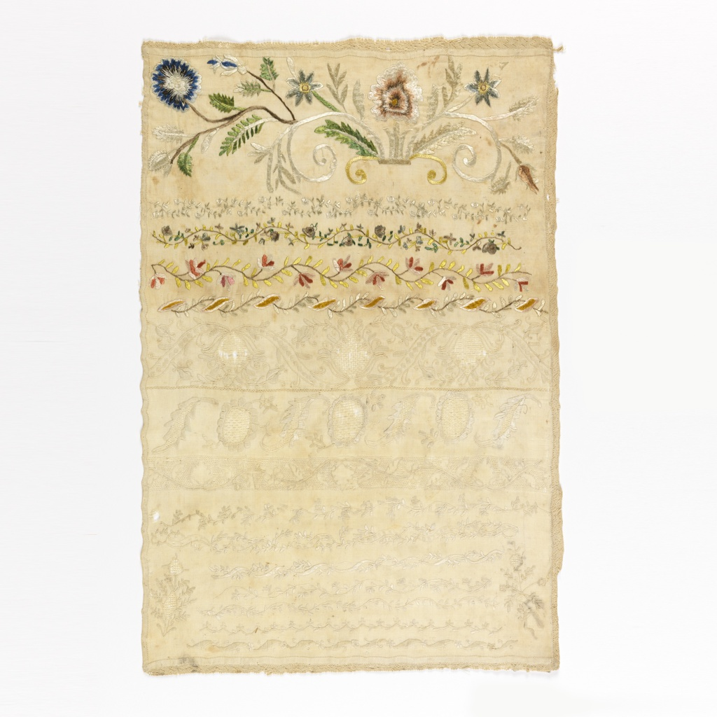 Flowers growing out of a scroll with cross borders in floral pattern.  Hemstitched on three sides; edged with narrow needlepoint lace on three sides.