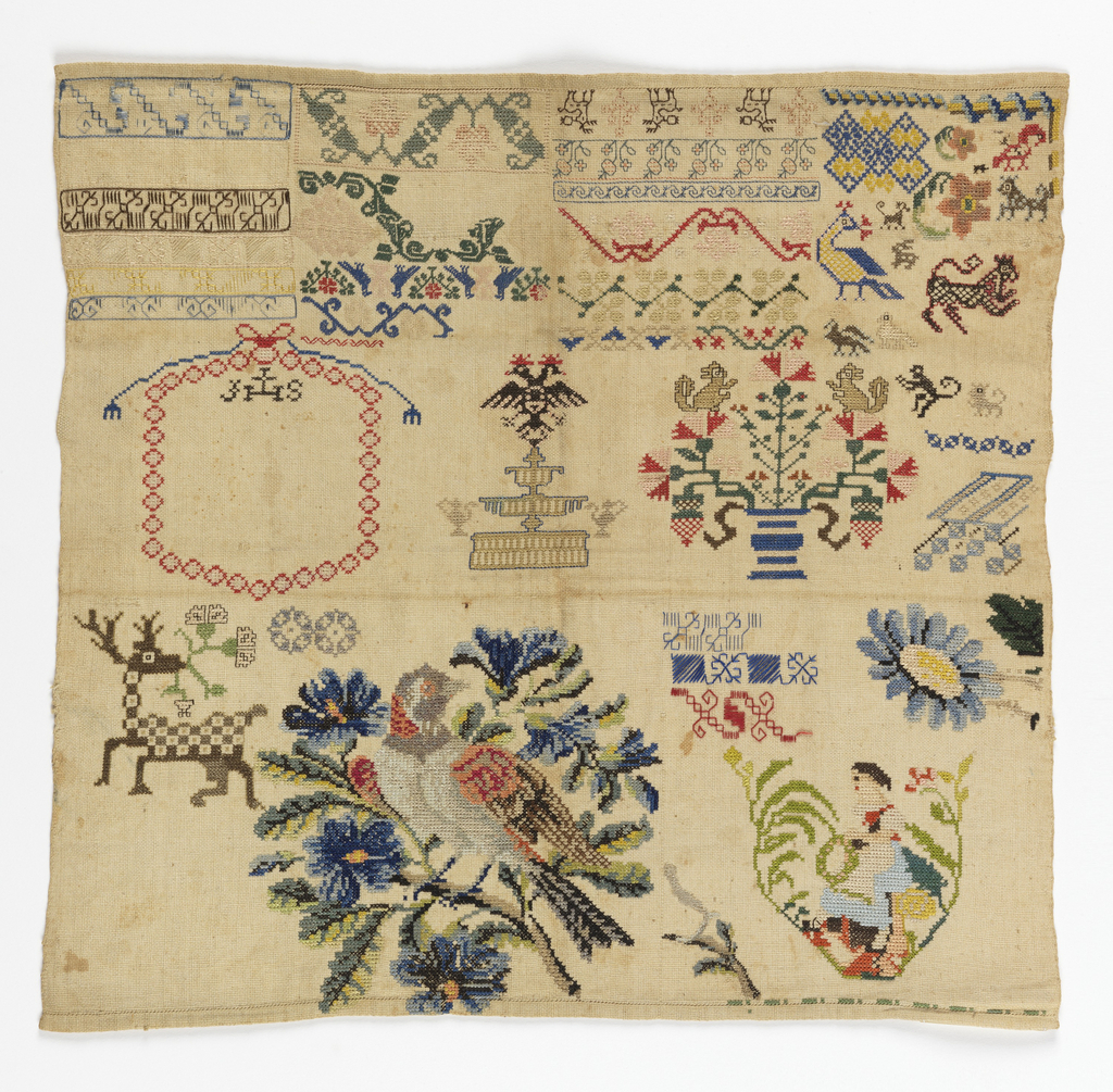 Square sampler in two sections. The upper register has bands of small scale geometric and floral patterns and spot motifs. The lower register has a deer, a bird on a flowering branch, and a girl in a pinafore with a wreath.