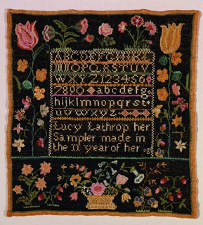 Embroidered in many colors on a black embroidered ground; a center panel with upper and lower case alphabets, numerals and the signature, and a wide floral border. The black background stops with an outer border of green cross stitch one row thick.