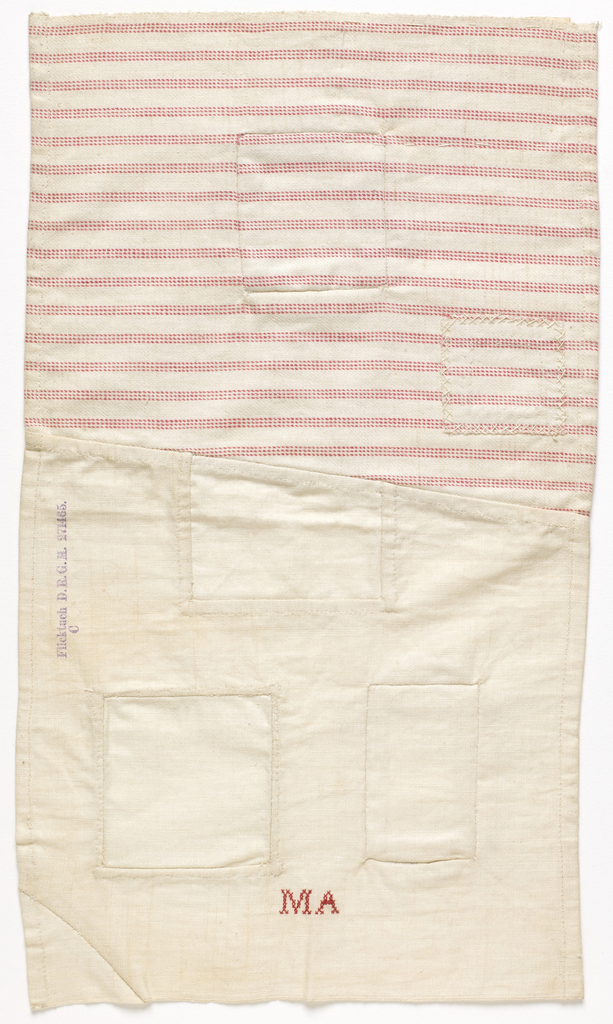 """Two pieces of fabric, one muslin and one red and white striped twill, stitched together at an angle. From them, five square holes have been cut and patched, plus one corner. Embroidered in red with the initials M.A. """"Flicktuch D.R.G.M. 271465"""" is printed on front. Label in German sewn to back."""