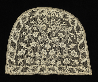 "Semi-circular cap crown in needle lace with a design of twisting vines and grapes. Commonly called ""Point d'Argentan"""