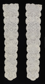 Pair of cap streamers in a design arranged around a series of diamond shapes, over and between which curves delicate floral designs. Smaller floral motifs fill square frames. Scalloped edges and ends.