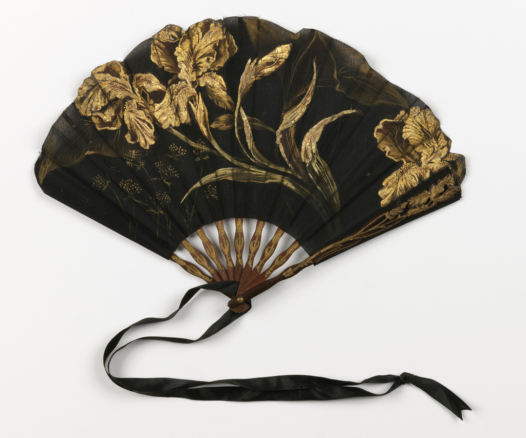 Pleated fan with leaf of gessoed and painted silk. Sticks of carved and incised mahogany with stamped gold flowers. Guards carved à jour with stamped gilt flower ornament. Fan leaf has a slightly arched shape