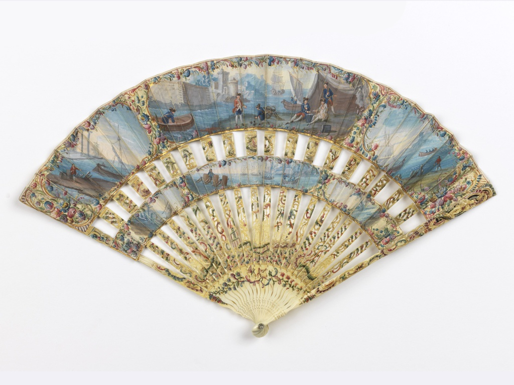 Pleated cabriolet fan with painted parchment upper and lowers leaves. The obverse shows naval scenes with floral borders.The reverse leaf is painted paper showing a woman in a pastoral landscape, with a rustic house and fence on the lower leaf. The sticks are carved and pierced openwork (à jour) with Chinoiserie figures, painted and gilded. Paste jewel set in both ends of the rivet.