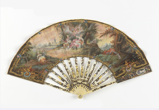 Pleated fan with painted leaf. The obverse mount shows a pastoral scene with a central group of a woman and a boy with two putti, one holding a torch. To the left is a girl and boy near a tree and on the right, a child plays with a dog. Gilt border with urns and wreaths. The reverse shows a girl seated under a tree and has a pink and blue floral border. Sticks have carved openwork (à jour) with figures of a man, woman, and putti, silvered and gilt. Guards have oval medallions with portraits of a man and woman, each holding a fan in an articulated arm made of painted ivory that moves using a lever to cover and uncover the face.