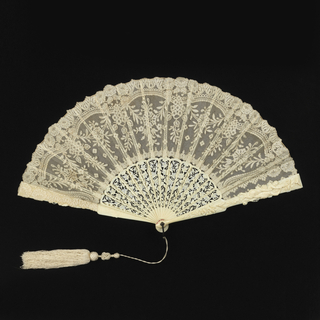 Pleated fan. Leaf ofwhite cotton bobbin-made Valenciennes lace in floral design, backed with silk net. Sticks of pierced and carved ivory in floral design. Guards with figures of birds, cupids and insects. Metal loop at the rivet. Attached tassel.