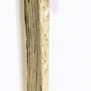Pleated fan with painted and gilded parchment leaf. Sticks of carved and pierced ivory fretted on edge to form pattern. Mother-of-pearl washer at the rivet.