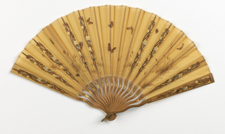 """Pleated fan. Leaf of saffron colored organdy painted with butterflies, marsh grasses and cattails in brown, copper and gold. Sticks of carved, pierced, and painted sandalwood. The box for the fan is marked """"Tiffany & Co., Union Square"""""""