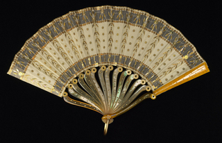Éventail de poche (pocket fan). Leaf of egg-shell mousseline de soie. Obverse: applied with band of the same material and gilt sequins of varying shapes. Shell-like sticks, each made of two separate pieces riveted together at shoulder forming a hinge and allowing the fan to be folded to half its length. Gorge shaped with S-curves and inlaid with round gilt piqués. Gilt metal bail.