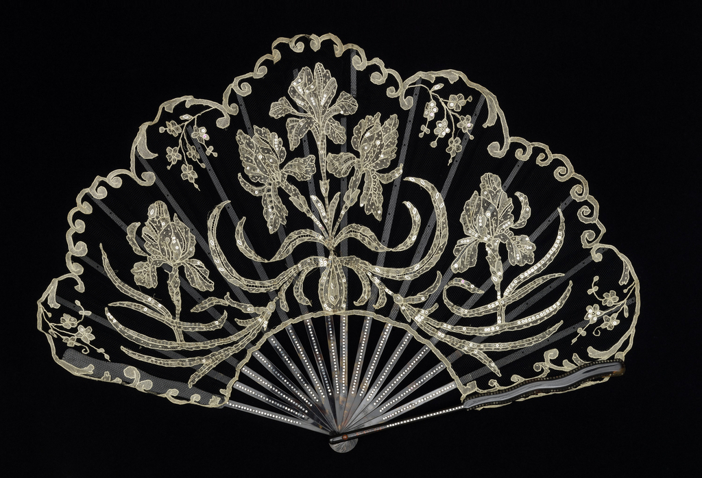 Pleated fan. Black silk net leaf with white cotton needle lace motifs of irises, scrolls and flower sprays applied; lace elements embroidered with silver-colored steel spangles. The sticks are of tortoise shell, piqué, with guards ending in a serpentine form; ebony slips; glass stone at the rivet.