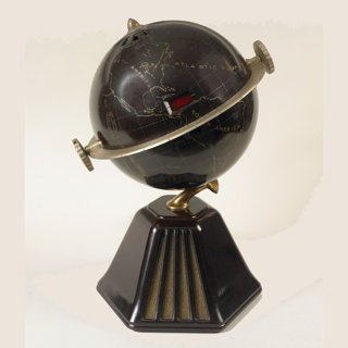 Brown globe on six-sided brown base. Continents, map grid, and continent and ocean names picked out in gold; gold-tone volume and tuning dials mounted on equator-like metal band encircling globe; small retangular station number read-out in center; gold-tone terminals at north and south pole positions. Two sides of base with vertical slits and fabric for speakers. Fabric-covered cord.