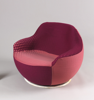 Nearly spherical armchair with cutout for seat and arms; covered in maroon and pink upholstery with Benday dot-like areas.