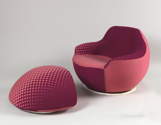 Amorphously-shaped foot stool covered in maroon and pink upholstery with Benday dot-like areas.