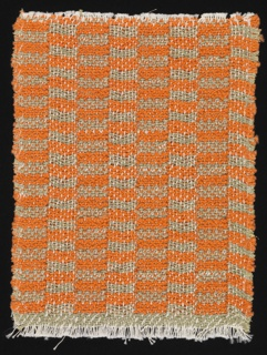 Handwoven sample for drapery material in a checkerboard of horizontal rectangles of orange and grey-green with an overall vertical stripe effect.   The warp is of white cotton used in pairs, bound with single wefts of orange bouclé yarn or paired wefts of one gray-green cotton with one gold metallic thread.  The lighter bands are double cloth with a pocketed structure; in the darker bands the two layers are locked together in a taquete structure. The vertical stripe effect is caused by the exchange of wefts from one face to the other.