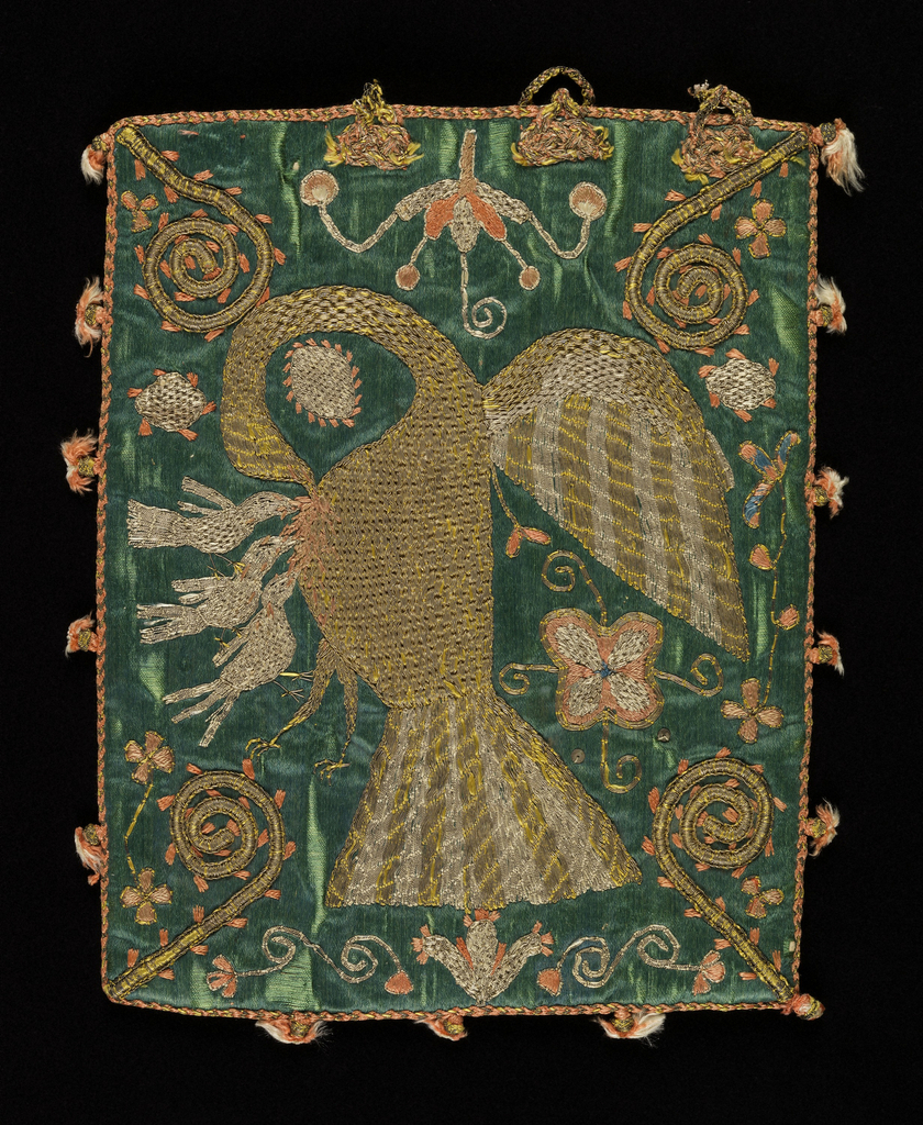 Flat rectangular bag of heavy green satin, embroidered in gold and silver metallic yarns and coral-colored silk. On one side the pious pelican is plucking her breast to provide sustenance for her young. Bishop's crooks point inward from the corners. On the other side, a stylized flowering branch in a pitcher, with animals and birds. The embroidery is worked through the satin into a heavy linen backing. Remains of loop and knot fastening at top; coral and gold cord edging, with small tassels at intervals; lined with coral silk taffeta.